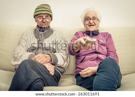 old couple watching television on the couch in the living room. concept about aging, old people, entertainment, humor and people - stock photo