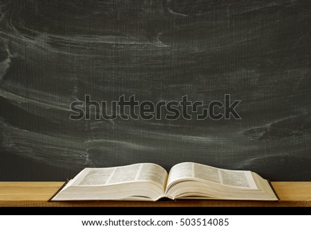 old covered text book, lying opened on a blank school or college classroom desk. Blackboard background. Mockup