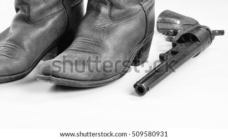 Old cowboy boots and old cowboy pistol in black and white with room for your type..