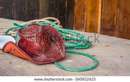 old cowboy hat and horse riding equipment on wood table. - stock photo