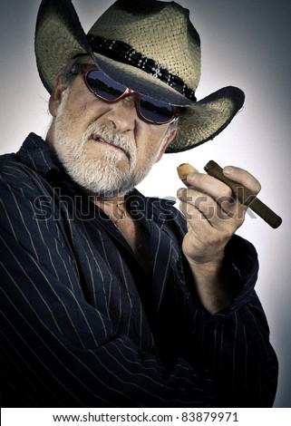 old cowboy men smoking a cigar - stock photo