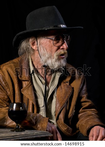 Old cowboy sitting with a glass of drink - stock photo