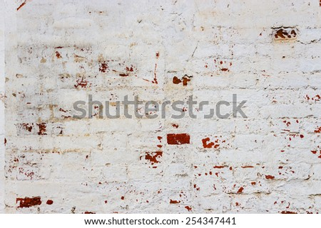 Old cracked red brick wall with traces of stucco - stock photo