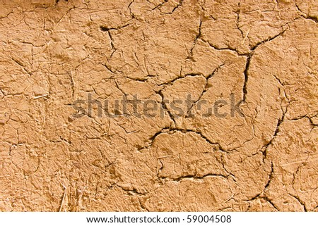 Old cracked wall made of orange clay and straw - stock photo