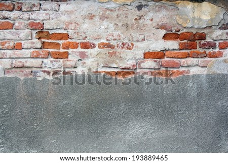 old cracked wall with cement and bricks on facade of ancient abandoned building - stock photo
