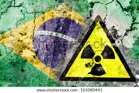 Old cracked wall with radiation warning sign and painted flag, flag of Brazil