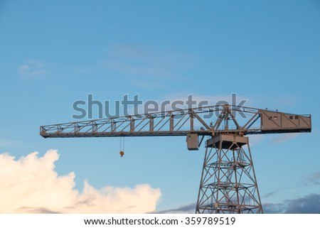 Old crane in harbor against sky at sunset - stock photo