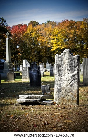 Old creepy churchyard during autumn season in high contrast color - stock photo