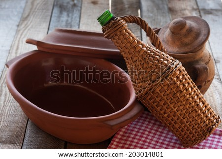 Old crocks with rattan bottle on old table