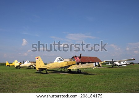 old crop duster airplanes on airfield - stock photo
