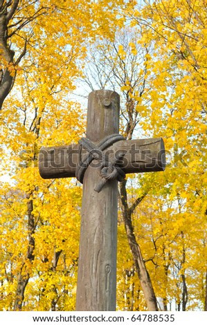 Old Cross at the Catholic Cemetery on Yellow Trees Background - stock photo