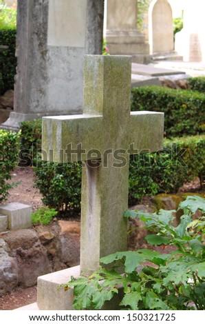 Old cross gravestone in a graveyard - stock photo