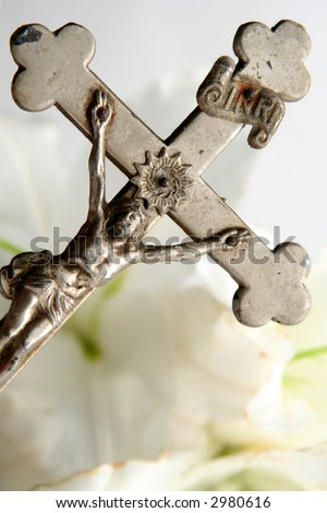 Old cross on white easter lilies background - stock photo