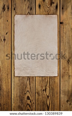 Old crumpled paper on a wooden wall. - stock photo