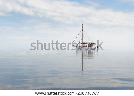 Old cutter anchoring in a misty sea. - stock photo