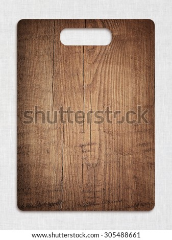 Old cutting board used for cooking on gray tablecloth. Wood texture. - stock photo