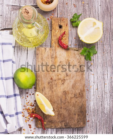 Old cutting board with a spicy red dried chilli, lemon and lime with a bottle of olive oil on a wooden background with herbs and light kitchen towel. selective Focus - stock photo