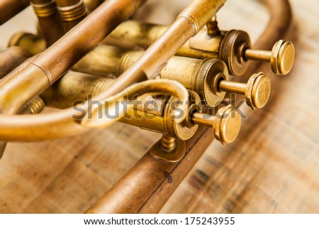 Old damaged brass trumpet photographed on papyrus. - stock photo