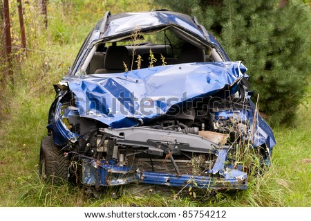 Old damaged rusty car wreck abandoned in the grass - stock photo