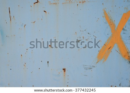 Old damaged rusty surface with X letter in a corner