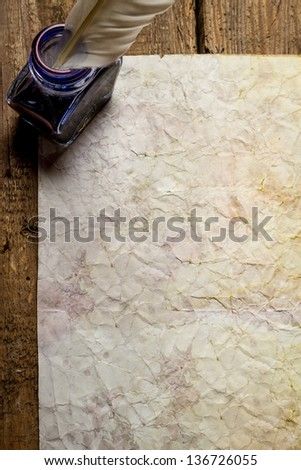 Old damaged sheet of paper with inkwells - stock photo