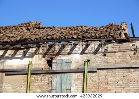 old damaged the roof of an abandoned house - stock photo