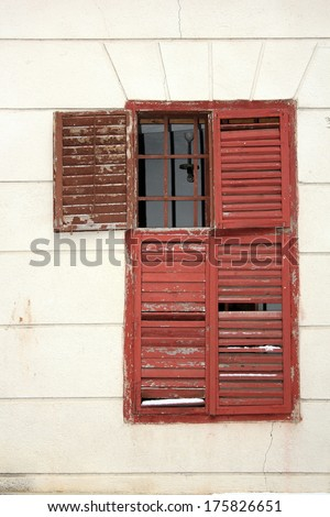 old damaged wooden blinds on an abandoned house - stock photo