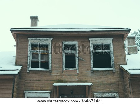Old dark abandoned house in winter forest - stock photo