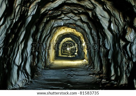 Old dark endless tunnel in the mountains with dramatic high contrast illumination - stock photo