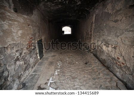 Old dark stone gateway perspective with glowing end. Tallinn, Estonia - stock photo