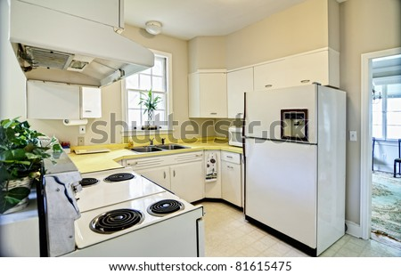 old dated kitchen with white appliances and yellow counters - stock photo
