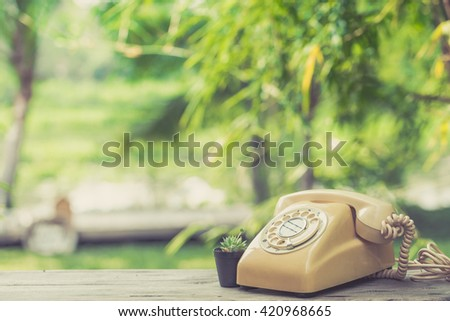 old day phone or rotary telephone on wood table in the garden with copy space - stock photo