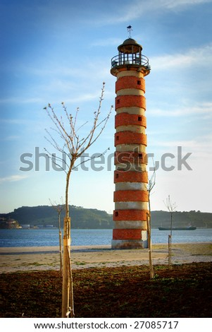 Old deactivated lighthouse in Lisbon by the Tagus river - stock photo