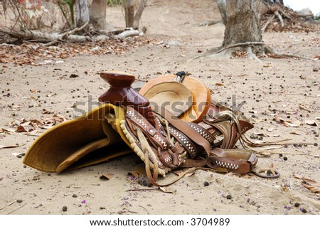 Old decorated mexican saddle lying on sand