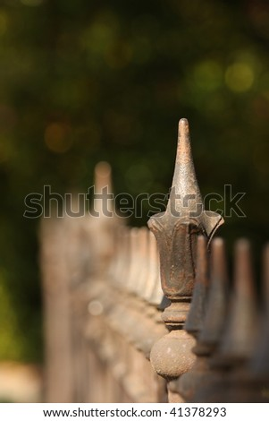 Old decorative iron fence in late afternoon light, with shallow depth of field receding into distance, with green trees behind. - stock photo