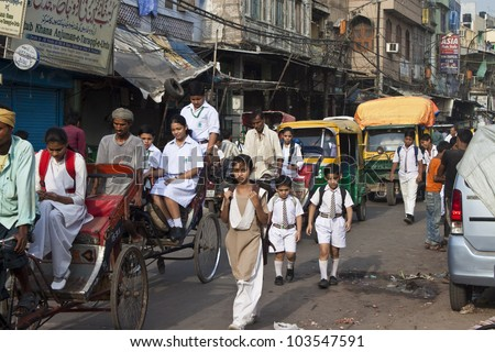 OLD DELHI, INDIA - AUGUST 3: Unidentified children on their way to a school at August 3, 2011 in Old Delhi, India.  Education is free for children for 6 to 14 years of age in India. - stock photo