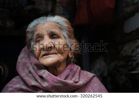 OLD DELHI, INDIA - FEB 15 : Unidentified an old Indian lady sitting at in front of his house at Chandi Chowk street with her traditional clothes, Old Delhi, India on February 15, 2015.