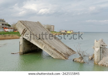 old demolished bridge over the river - stock photo