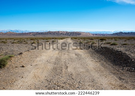 old desert dirt road in the northwest, distant mountainous - stock photo