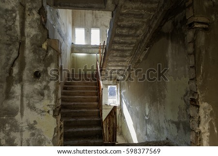 Old destroyed concrete, stone staircase in interior of ruins of unfinished administrative building of business center. Ruined old staircase in interior of abandoned factory building. Trash industrial