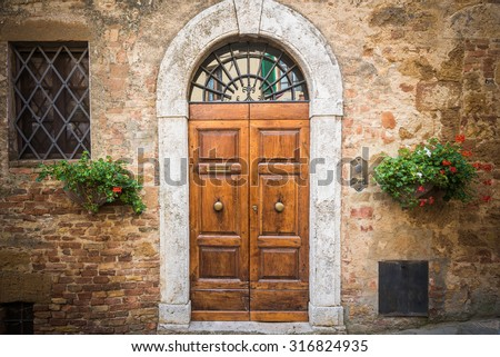Old destroyed door to the Tuscan home - stock photo