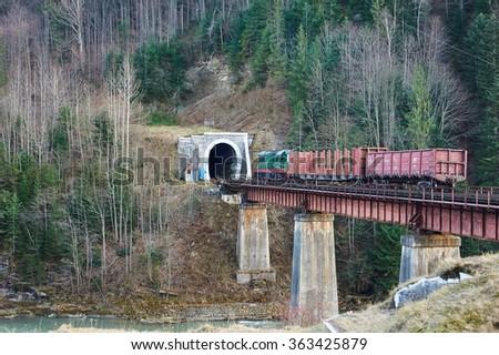 Old diesel cargo train in tunnel. Mountain railroad in Yaremche, Ukraine - stock photo
