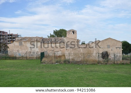 Old Dilapidated Mediterranean Style  Building in Spain with New Construction in the background