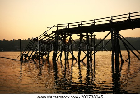 Old dilapidated wooden bridge in name Mon Bridge broken down in the river at the Sangkhla Buri district ,Kanchanaburi province in Thailand - stock photo