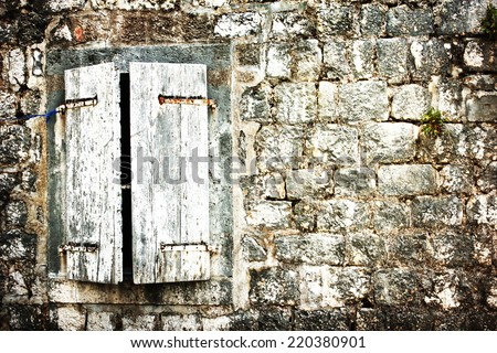 old dirty background of closed window with old wood shutters  window on old dirty wall  - stock photo
