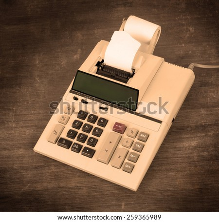 Old dirty calculator on a wooden desk - warm yellow filter - stock photo