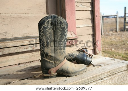 Old dirty cowboy boots with spurs on rustic front porch - stock photo