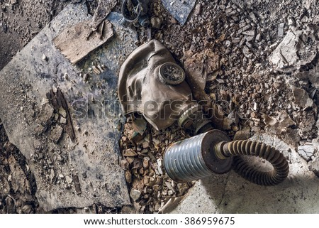 Old dirty gas mask lying on messy industrial ground - stock photo