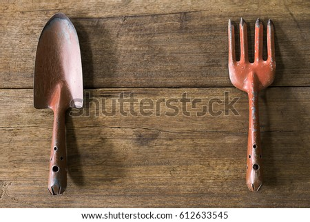 Old dirty grunge rusty gardening tools on dirty grunge wooden background in vintage style