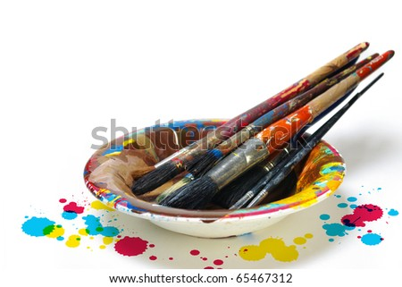 Old dirty painting brushes resting in a colorful plate